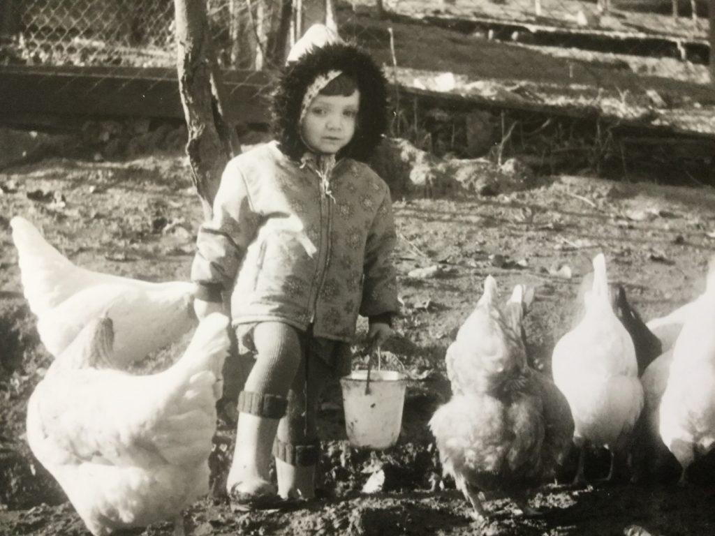 Sonja Eisenbeiß als Kind mit Hühnern und einem Futtereimer vor einem Baum im Gehege